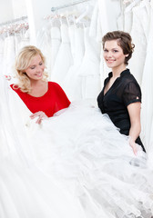 Two girls compare the wedding dress preparing to try it on