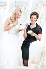 Shop assistant and the bride eat a delicious cake