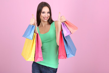 Beautiful young woman holding shopping bags on pink background