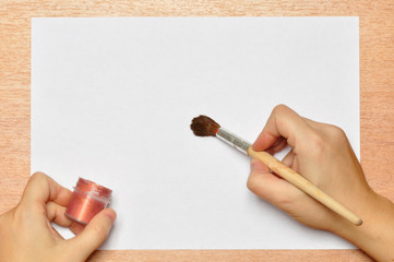 Paint Brush in hand on paper background.