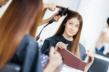 Reflection of beautician doing hair style for woman