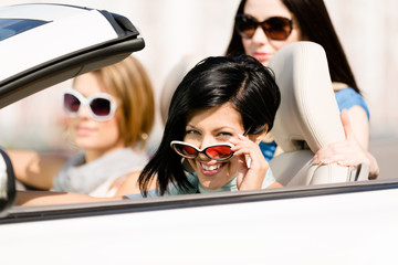 Group of happy girls in the convertible car
