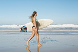 Teenage girl walking on the beach with her surfboard