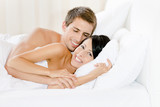Man lying in bedroom with white linen embraces woman