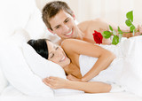 Man lying in bed gives red rose to woman