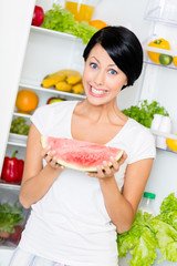 Woman takes watermelon from the opened refrigerator