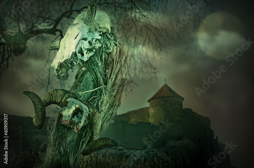 Gothic skull near the old fortress with the Moon