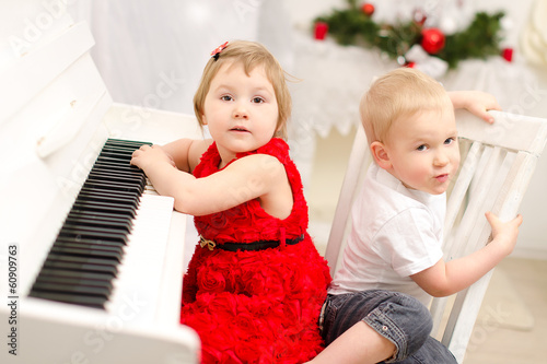 boy and girl playing on white piano