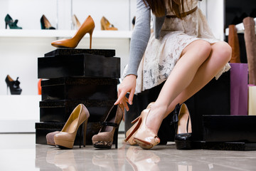 Female legs and variety of shoes in the footwear shop