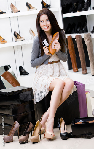 Woman hands shoes and credit card in the footwear shop