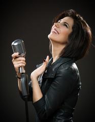 Half-length portrait of female rock musician in black jacket