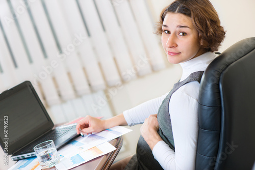 Young pregnant woman working at office