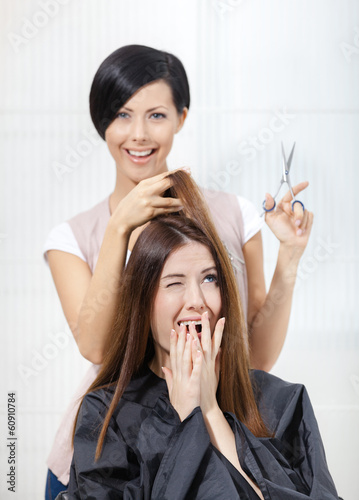 Hairdresser cuts hair of woman in hairdressing salon