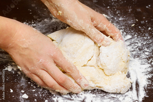 female hands kneading dough