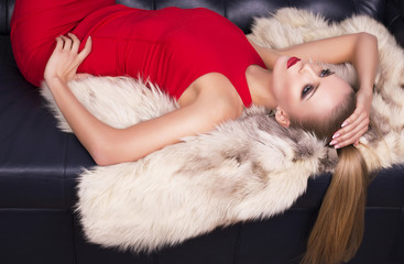 sexy girl with blond hair in red dress lying on fur coat