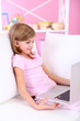 Little girl sitting with laptop on sofa in room