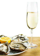 Oysters in a white plate with lemon and a glass of wine