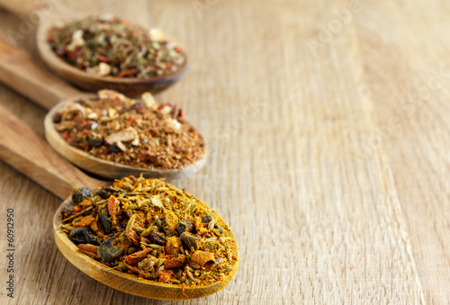 Spices in wooden spoons on a wooden board