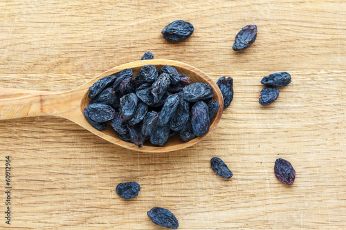 Wooden spoon with raisins on a wooden board