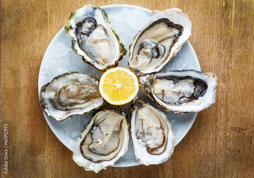 Fotobehang Schaaldieren Fresh oysters in a white plate with ice and lemon