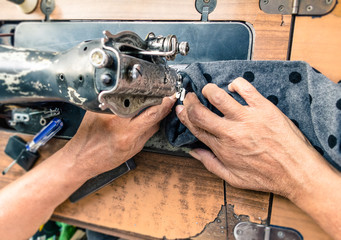 Old working hands at sewing machine