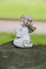 Kleiner Engel betet auf Grabstein am Wegesrand