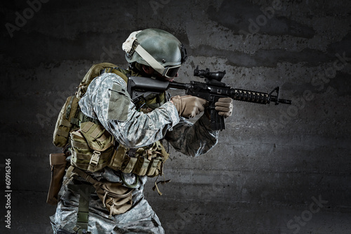 Soldier with mask aiming a rifle