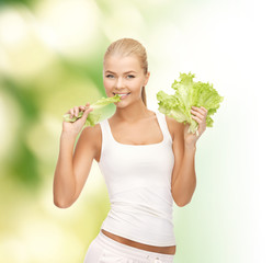 smiling woman biting lettuce