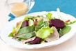 Fresh salad with lettuce leaves, boiled beef, beet, sauce
