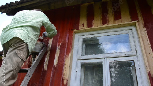 Painter man on ladder paint wood house wall with brush window