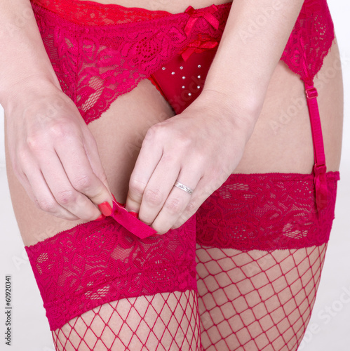 Woman fastening suspender to her stockings