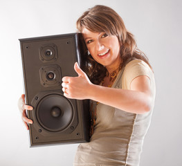 Beautiful woman holding big wooden speaker