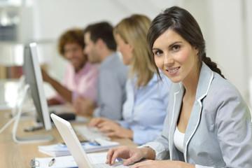 Smiling businesswoman working on laptop