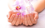 beautiful manicure with pink orchid on the white towel