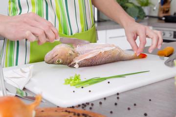 Frischen Fisch filetieren - Frau zerlegt einen Speisefisch