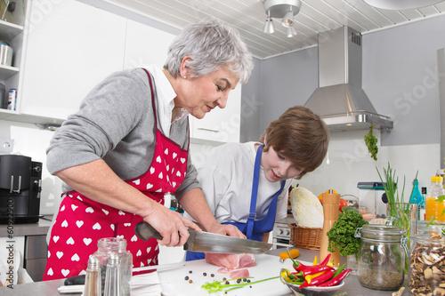 Familie: Enkel mit der Großmutter in der Küche beim Kochen