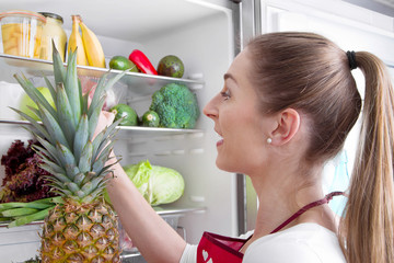 Frau legt Wert auf gesunde Ernährung - vor dem Kühlschrank