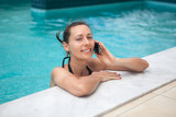 Woman on the phone while relaxing in pool