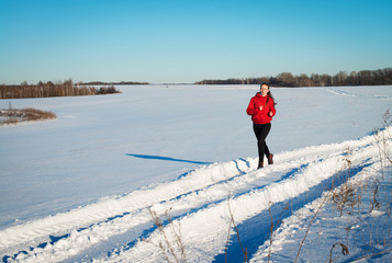 Young girl runner. Winter nature.