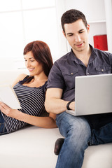 Portrait of a cheerful couple,looking into laptop and smiling.