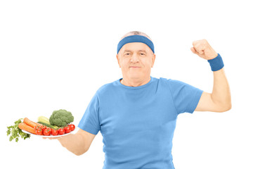 Mature man holding plate full of vegetables and showing strength