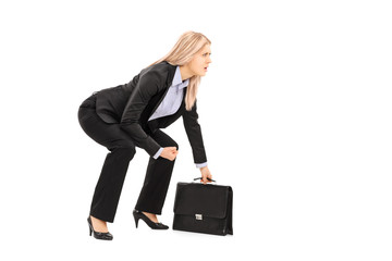 Young businesswoman in sumo wrestling stance holding suitcase