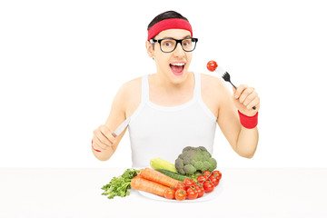 Young man with glasses eating vegetables