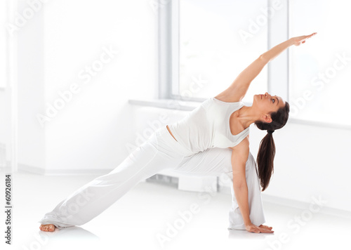 Fit young woman spending yogatic time by herself in room