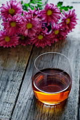 glass of cognac and flowers