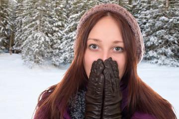 Junge Frau friert im Winter in einem Wald mit Schnee