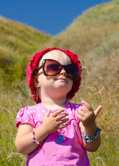 Cute Baby with Sunglasses Posing on Hill Background