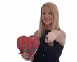 Young girl holding a Valentines Day heart pointing