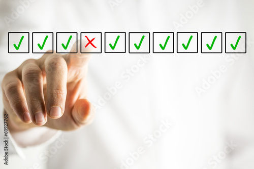 Man selecting a cross from a line of check marks