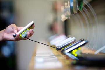 Picking up a mobile phone from a shelf in a shop